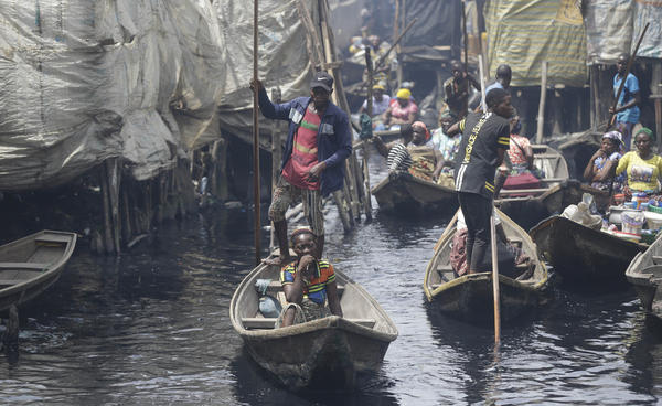 People travel by canoe in a poor neighborhood in Lagos, Nigeria. Lockdowns have begun in Africa as coronavirus cases rise. Nigeria has reported just over 100 coronavirus cases, though the actual number is likely much higher.