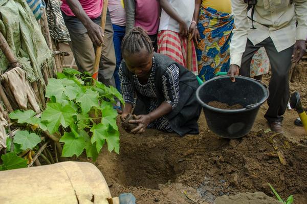 Kathungu Kinyatole plants a tree to honor a loved one she lost to the Ebola virus.