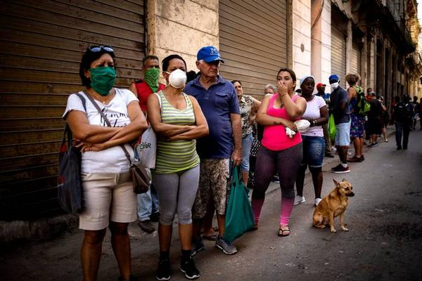 PANDEMIC PROBLEMS Cubans wearing masks to ward off coronavirus line up to buy food in Havana last week as more economic hardship mounts due to the crisis.