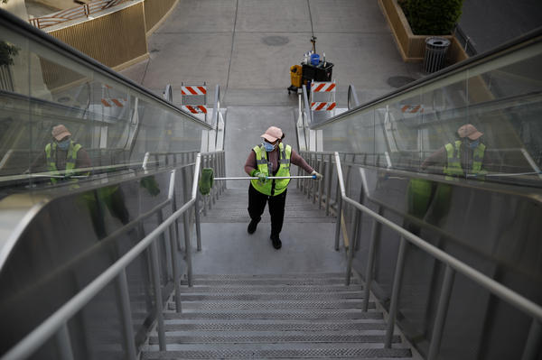 A worker cleans an area along the Las Vegas Strip that's now devoid of the usual crowds, with casinos and many other business shuttered.