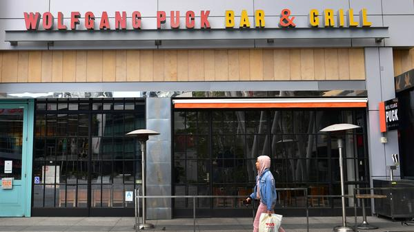 A pedestrian walks past a closed Wolfgang Puck Bar & Grill restaurant in Los Angeles. President Trump has suggested changing tax deductibility law as a way of helping the restaurant industry.