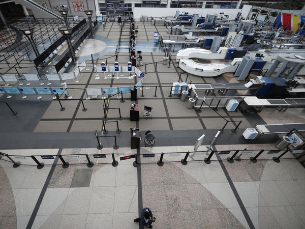 A lone passenger walks past the north checkpoint at Denver International Airport on April 1, which was closed because of a lack of traffic as a statewide stay-at-home order remains in effect to help reduce the spread of the coronavirus.