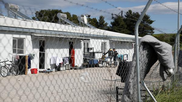 Migrants gather outside at a refugee camp in Ritsona, north of Athens, on Thursday. Greek authorities have placed the camp under a 14-day quarantine, after at least 20 residents tested positive for COVID-19 infection.