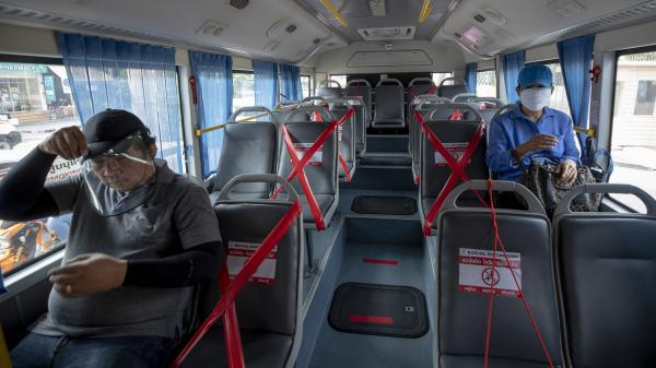 Bus passengers in Bangkok Friday morning. Thailand's prime minister announced a nationwide 10 p.m.-to-4 a.m curfew starting Friday to combat the spread of the coronavirus.