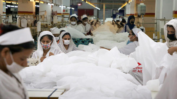 Workers in Dhaka sew protective suits at a garment factory during Bangladesh's lockdown.