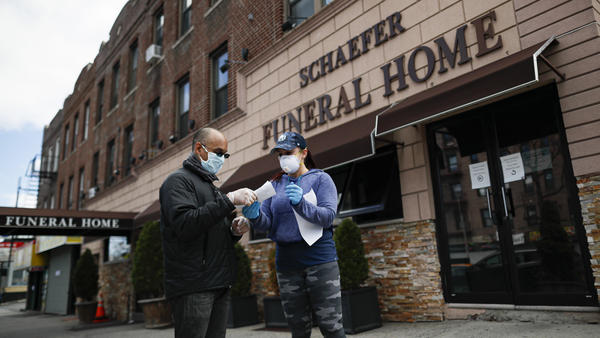Employee Gina Hansen (right) hands documentation to a client outside the Daniel J. Schaefer Funeral Home in Brooklyn on Thursday.