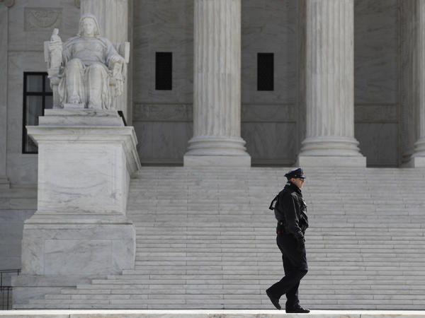 A police officer walks outside the Supreme Court on March 16.