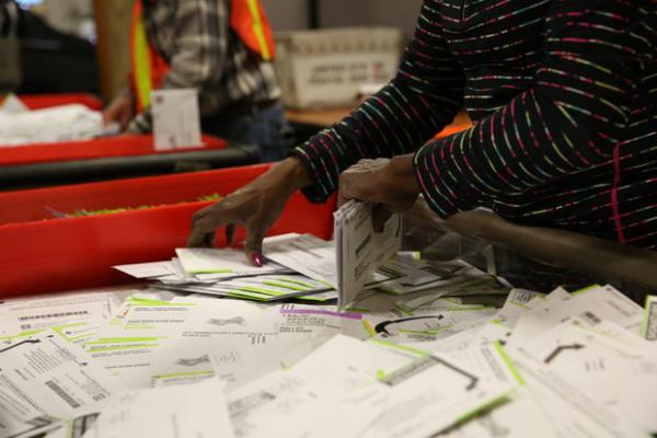 <p>A Multnomah County elections worker sorts ballots.</p>