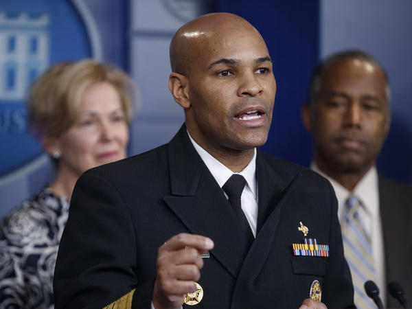 "U.S. Surgeon General Jerome Adams, shown here during a news conference at the White House last month, said Tuesday that he expects some places to be able to ""slowly reopen"" after the end of April."