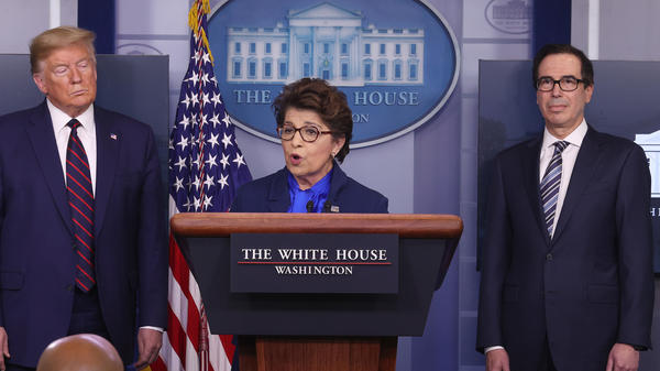 Small Business Administration chief Jovita Carranza speaks at the White House as President Trump and Treasury Secretary Steven Mnuchin look on. Some small business owners are facing delays in applying for a new loan program.