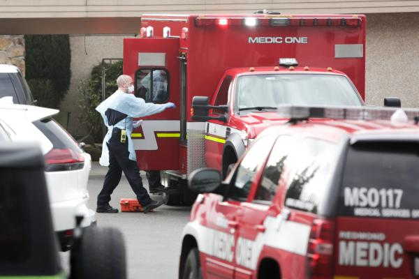 Ambulance staff prepare to transport a patient from the Life Care Center nursing home where some patients have died from COVID-19 in Kirkland, Washington.
