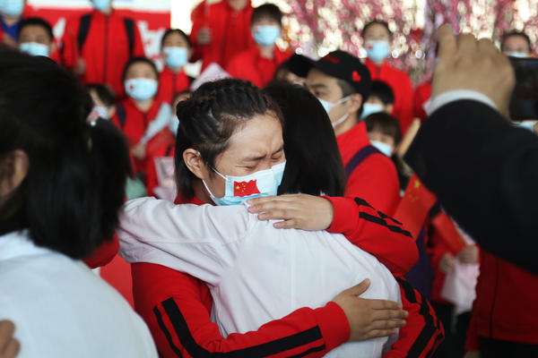 Health workers from Wuhan's Tongji Hospital share an emotional embrace with their peers from a hospital in Jilin province at the Tianhe Airport. Colleagues who worked on the front lines together for the past two months bid farewell as Wuhan lifts the lockdown on Wednesday.
