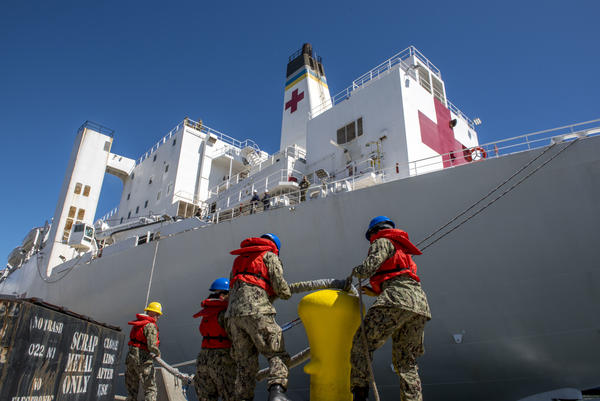 Sailors remove the lines off the bollard as the USNS Mercy hospital ship prepares to depart Naval Base San Diego, March 23.
