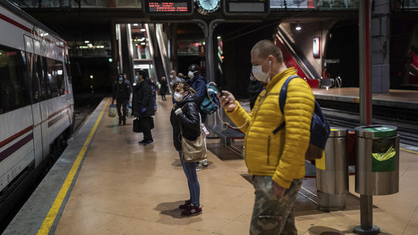 Commuters wearing face masks to protect against coronavirus at the platform of Atocha train station in Madrid, Spain, on Monday. Spain has begun easing restrictions as the number of new cases declines.