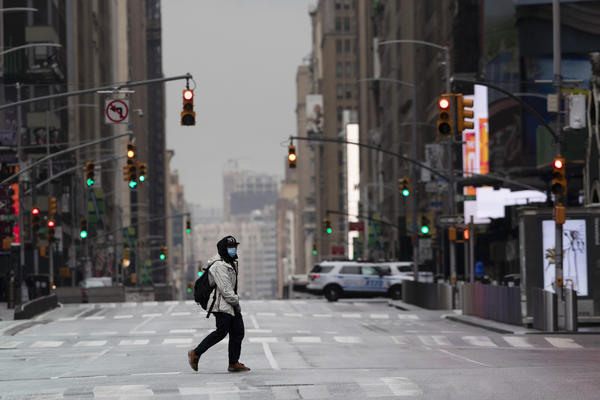 A man wearing a mask crosses the street in a quiet Times Square in New York City on April 9. The coronavirus outbreak has exposed racial divisions in the U.S. — as well as geographic ones.