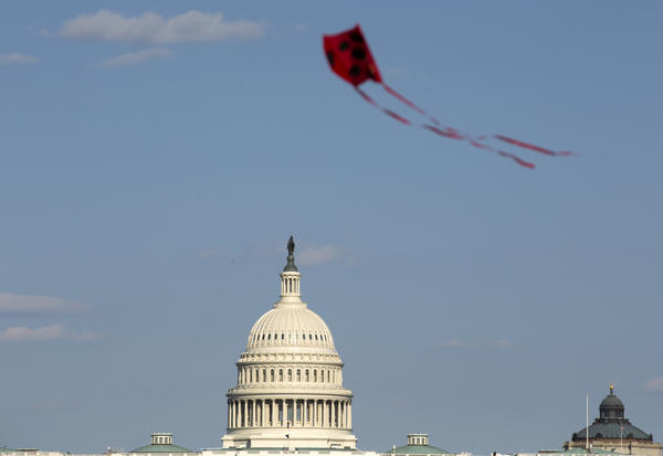 The U.S. Capitol is viewed as a kite flies at the National Mall in Washington earlier this month. Both the House and Senate delayed their return to Washington and leaders are now saying Congress is not expected to return before May 4.