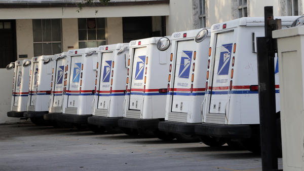 U.S. Postal Service trucks are lined up in Miami Beach, Fla. The agency says that without emergency funding from Congress, it could run out of money within months.