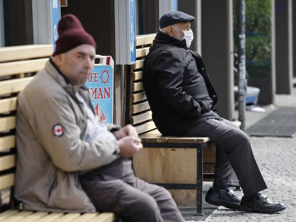 Germany's social distancing requirements have been extended to May 3, but the country is taking steps to re-open parts of public life. Here, two men sit at a distance in Berlin's Kreuzberg district on Wednesday.