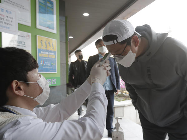 A man wearing a face mask to help protect against the spread of the new coronavirus has his temperature checked upon his arrival to cast his vote for parliamentary at a polling station in Seoul, South Korea, on Wednesday.