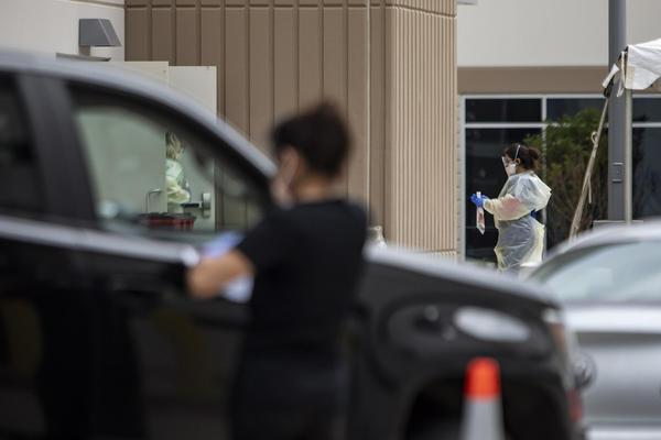 A health worker screens a driver at a drive-thru COVID-19 testing site in South Austin.