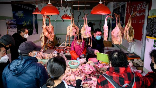 People wearing protective face masks shop at a chicken stall at a wet market in Shanghai on Feb. 13.