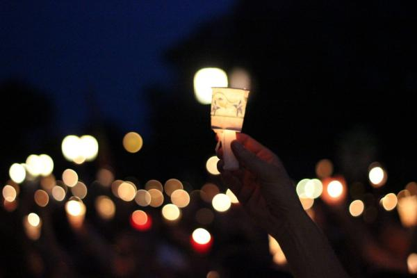 A person holds a makeshift paper lantern at the Vigil Against Violence in Lincoln, Nebraska, on July 22, 2012.