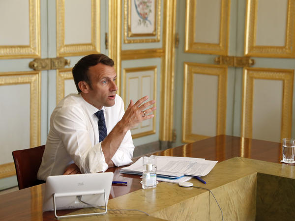 French President Emmanuel Macron attends a video conference call with French virologist Françoise Barré-Sinoussi on efforts to develop a vaccine and treatment against the new coronavirus, at the Elysee Palace in Paris, Thursday.