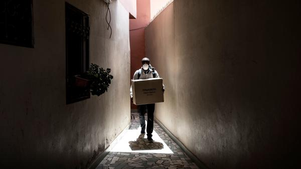 A man carries a box of protective masks to emergency workers Thursday in Dakar, the capital of Senegal. The West African country has seen relatively few confirmed cases of the coronavirus to this point — but global health officials fear that won't always be the case.