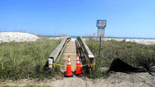 """Police tape and pylons block the public access to Jacksonville Beach last month amid the coronavirus outbreak. The mayor of Jacksonville, Fla., says parks and beaches in Duval County would reopen Friday for """"essential activities"""" only."""
