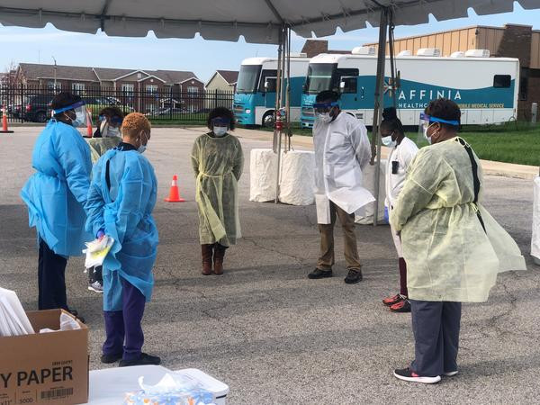 Affinia Healthcare's staff take a moment for prayer before the first day of testing at their north St. Louis location on April 2. Long-standing socioeconomic factors have disproportionately put African Americans in the region at risk for COVID-19.