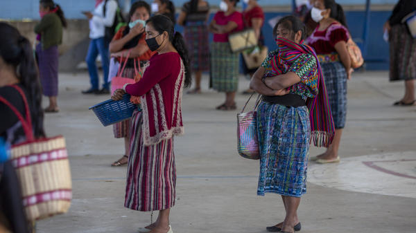 Women wearing face masks stand at a safe distance to help curb the spread of the new coronavirus, as they wait for food assigned to their children outside a school in Xesuj, Guatemala, where many residents depend on remittances, largely from the U.S. The fallout from the pandemic is cutting into the financial lifelines for people across Latin America, Africa and Asia.