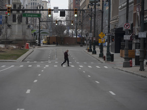 A man crosses an empty street in Detroit, Michigan on March, 24, 2020. - At 12:01 am Tuesday March 24,2020 Governor Gretchen Whitmer ordered a 'Stay at Home and Stay Safe Order' to slow the spread of Coronavirus (COVID-19) across the State of Michigan which now has 1,791 confirmed cases and 24 deaths due to the virus.