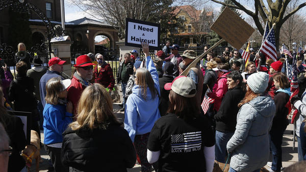 Protesters gather outside Minnesota Gov. Tim Walz's official residence in St. Paul on Friday, calling for him to loosen stay-at-home restrictions imposed because of the coronavirus.