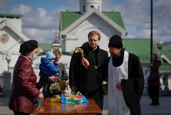 An Orthodox priest blesses traditional Easter cakes and painted eggs in preparation for Easter, outside a church in Minsk, Belarus on Saturday.