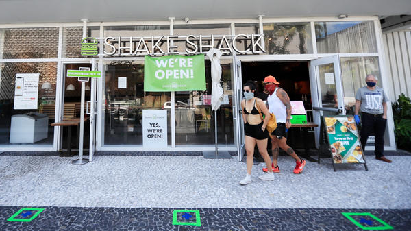 Shake Shack is returning a $10 million loan to the Small Business Administration, saying the money should go to restaurants that need it more. Here, customers wait for to-go orders outside a Shake Shack in Miami Beach, Fla.