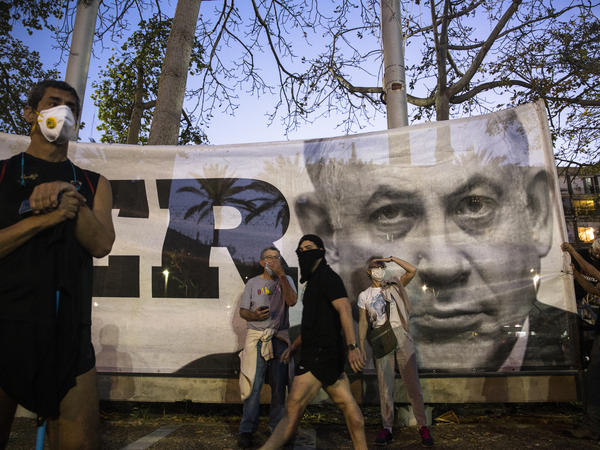 Israeli Prime Minister Benjamin Netanyahu, shown here on a banner at an anti-corruption rally on Sunday, has reached a deal for a unity government with his rival Benny Gantz.