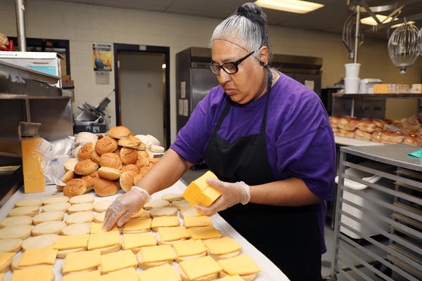 A Kansas City Public Schools food service employee prepares meals to pass out to students on March 19, 2020. Nationally, school meal distribution is only reaching about 20% of families whose kids would normally receive free breakfast and lunch at school.
