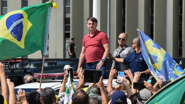 Brazilian President Jair Bolsonaro prepares to speak to supporters protesting against quarantine and social distancing measures to combat the new coronavirus outbreak in Brasilia on Sunday.