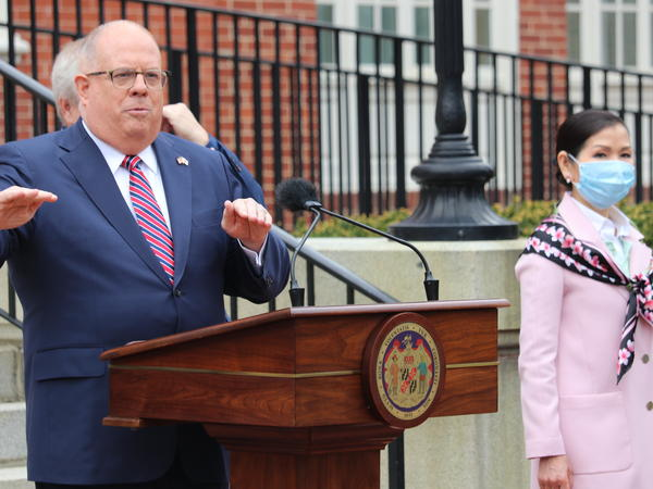 Maryland Gov. Larry Hogan speaks at a news conference on Monday in Annapolis, Md., with his wife, Yumi Hogan (right), where the governor announced Maryland has received a shipment from a South Korean company to boost the state's ability to conduct tests for COVID-19 by 500,000.