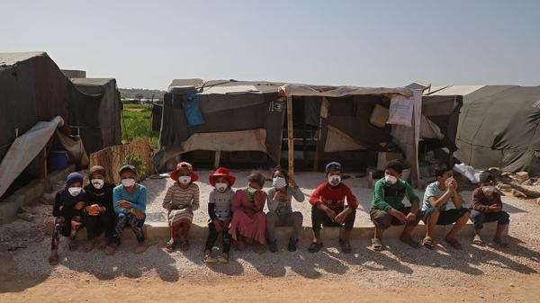 "Children displaced by the war in Syria's Idlib province sit, wearing face masks during a COVID-19 awareness campaign this week in Dana. The World Food Programme warned that people living in displaced-person camps could be ""particularly vulnerable"" to the pandemic's physical and economic effects."