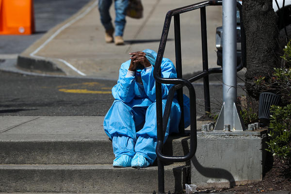 A fatigued health care worker takes a moment outside the Brooklyn Hospital Center in April. Many hospital workers these days have to cope with horrific tragedies playing out multiple times on a single, 12-hour shift.