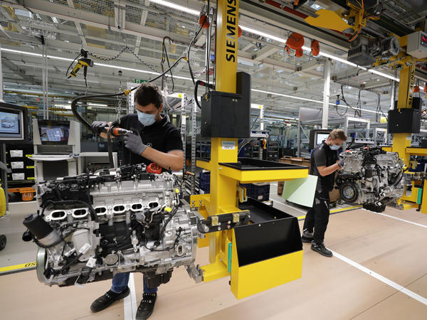 Employees assemble motors at a Mercedes-Benz factory in Stuttgart, Germany, on Wednesday. The German government pays much of laid-off workers' salaries for up to 12 months during economic crises.