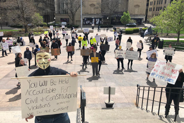 About 75 people wearing masks and carrying signs protest outside the Ohio Statehouse on Thursday, April 9, 2020, in Columbus, Ohio. The protesters criticized the state's shutdown of the economy over the coronavirus crisis.