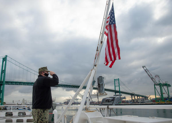 Sailor John Arkulary from Marshfield, Wis. salutes the flag aboard the hospital ship USNS Mercy in Los Angeles April 13.