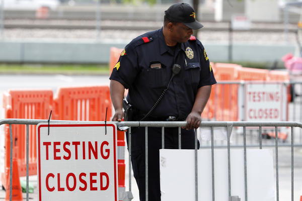 Sergeant K. Pope with Dallas police places a barricade in front of a coronavirus testing site advising the site is closed for the day in Dallas.