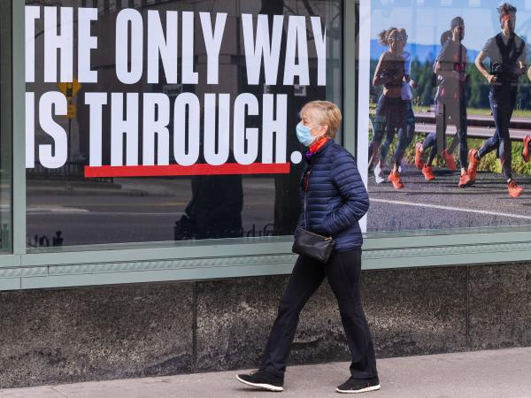 A person wearing a face mask walks down a mostly empty Michigan Avenue in Chicago Thursday. In all major political groups, most people say they support shelter-in-place orders to fight the COVID-19 pandemic, according to a recent poll.