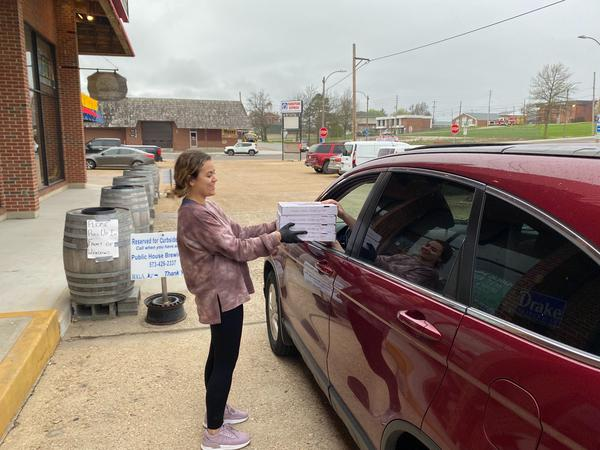 A Public House Brewing Company employee brings pizza to a curbside customer. It's a small business trying to make it in a college town where the students have largely left town.