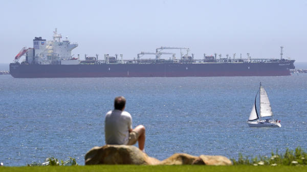 The oil tanker Pegasus Voyager sits off the coast as a man sits and watches in a park in Long Beach, Calif., on April 22. Many vessels are parked between Long Beach and the San Francisco Bay Area with nowhere to go due to lack of demand and nowhere to store the oil.