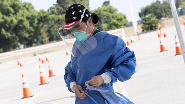 A health worker dons protective gear at a drive-through COVID-19 testing site set up by the Los Angeles Fire Department in Inglewood, Calif., on Monday. The Trump administration has released new guidelines on testing.