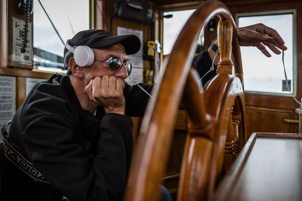 Jaroslaw Gniatkowski, who is blind, holds the steering wheel with headphones on to hear commands from a computer with information about course and rudder position.